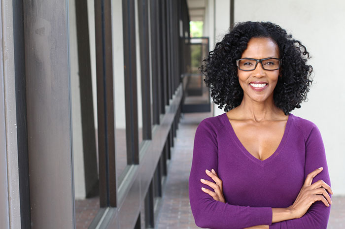 Female Entrepreneur wearing purple top and glasses