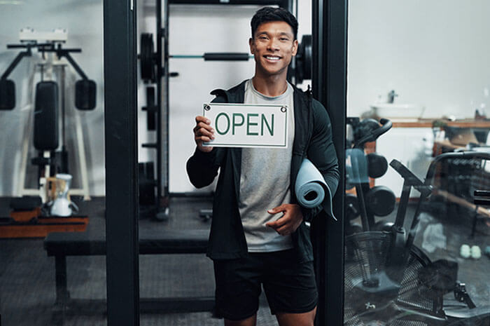 gym owner holding open sign